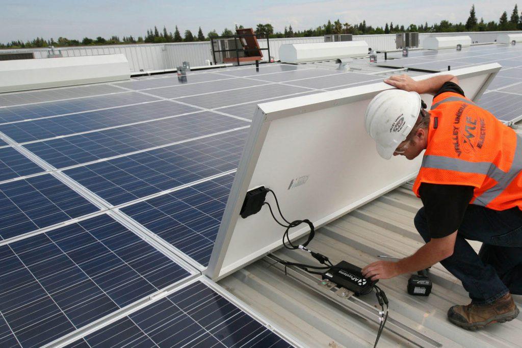 Technik sprawdza działanie mikroinwertera pod panelem solarnym